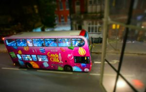 London, England - Dec 12, 2014: Captured from a window on Lower Sloane Street, one of the famous double-decker buses of London is seen, dressed fully with a pink colored Candy Crush game application advertisement of Facebook.